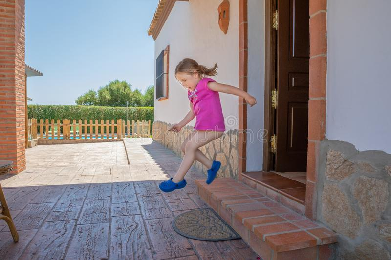 Happy little girl taking a big leap at home stock image