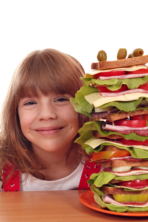 Happy little girl with tall sandwich stock photography