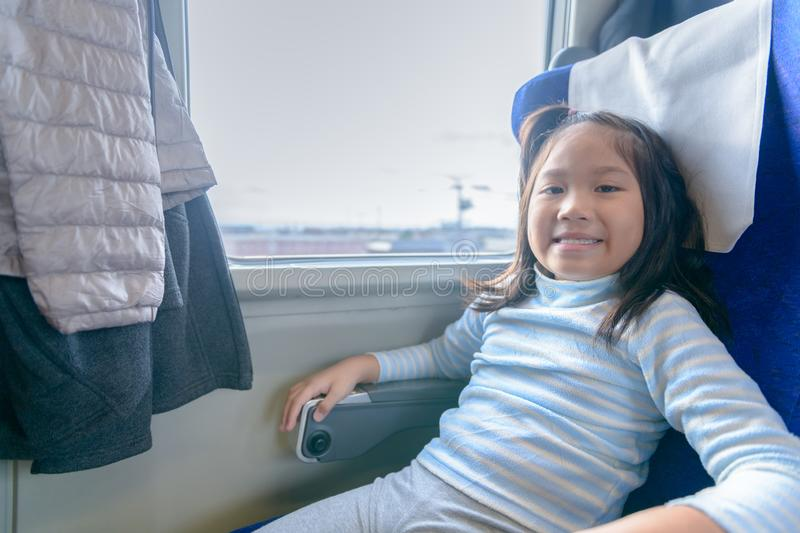 Happy girl traveler smile and sit in the train royalty free stock photo