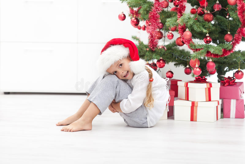 Happy Little Girl Under The Christmas Tree Stock Photo
