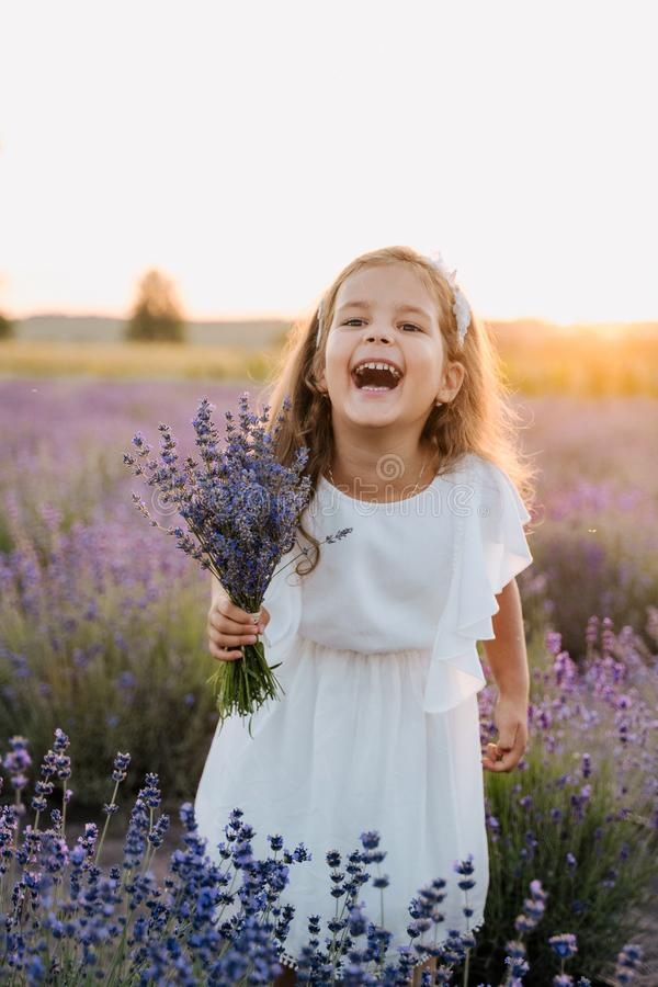 Happy Little Girl with Violet Lavender Bouquet. Joyful Fun Kid Holding Bunch of Flowers. Caucasian Child Model Laughing at Camera. Blooming Meadow, Countryside royalty free stock photos