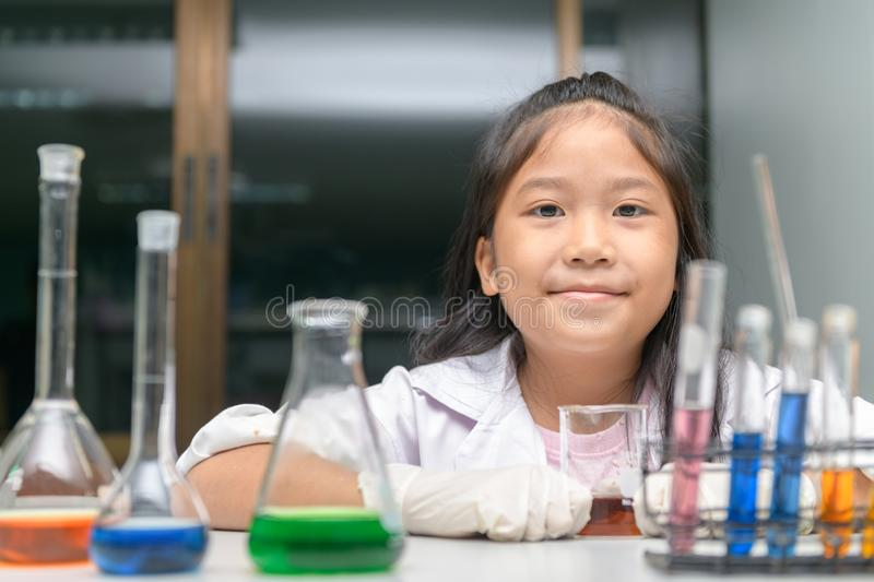 Happy little girl wearing lab coat making experiment royalty free stock images