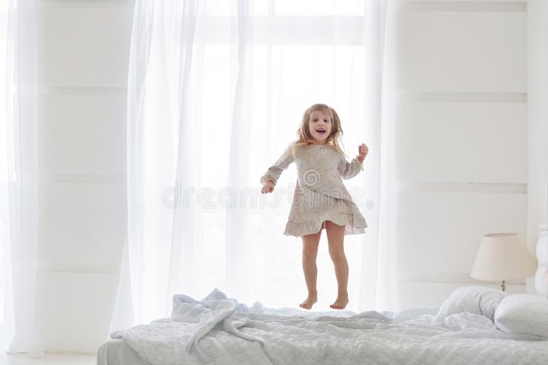 Happy little girl wearing white pajamas jumping on bed in white bedroom stock image