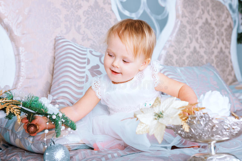 Happy little girl in white dress decorates tree in the Christmas decorated room stock photos