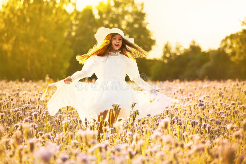 Happy little girl in a white dress running on field at sunset royalty free stock photos