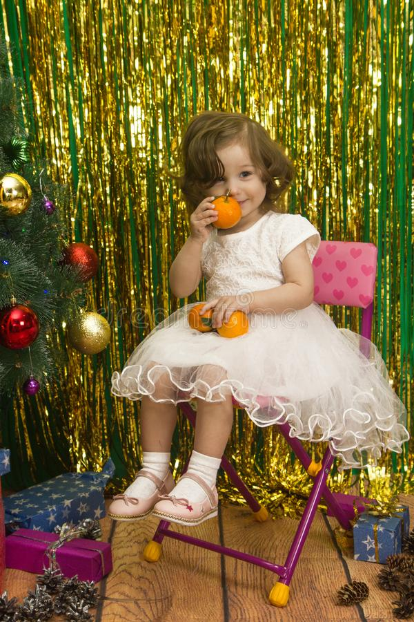 Happy little girl in white dress sit on chair christmas backgro stock images