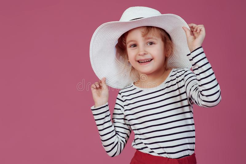 Happy little girl in white hat at pink studio background royalty free stock photography