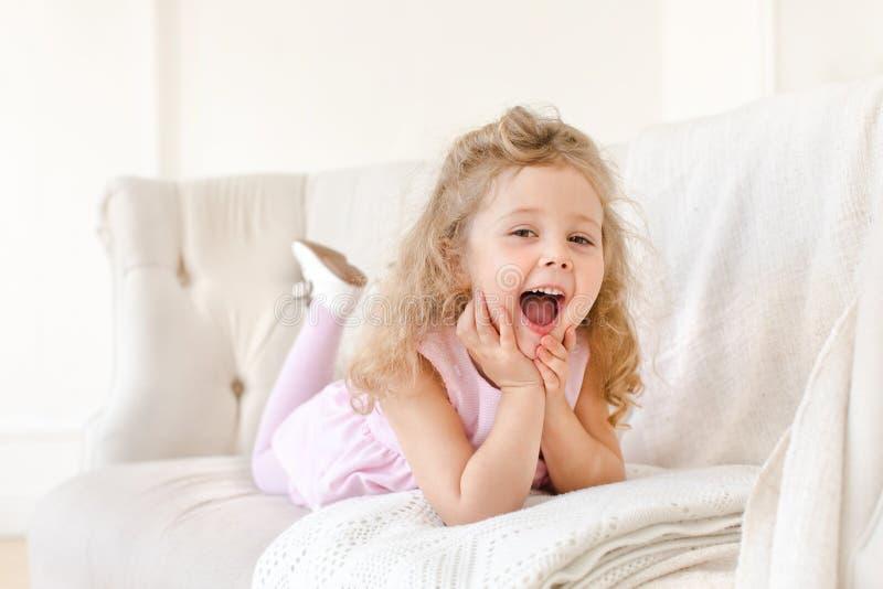 Happy little girl on white sofa stock photo