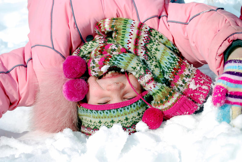 Happy little girl in winter clothing upside down royalty free stock photos