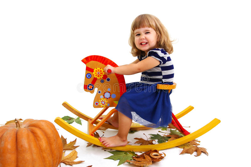 Happy little girl on wooden horse stock image