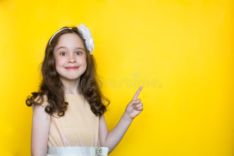 Happy little girl on yellow background points her finger at the space for lettering. Concept of education stock photos