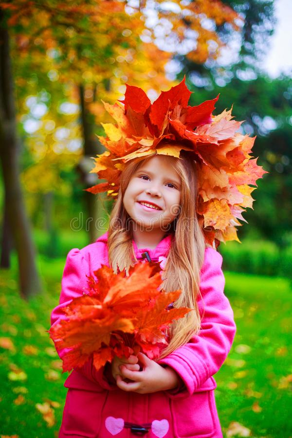 Happy little girl with yellow and red autumn leaves royalty free stock photo
