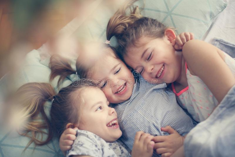 Happy little girls in bed. Three little girls lying in bed and hugging. Space for copy royalty free stock photo