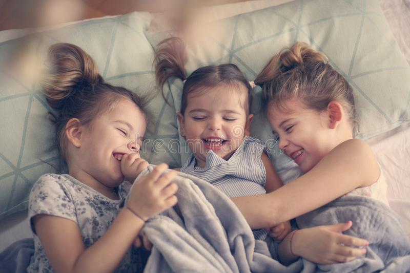 Happy little girls in bed. Three little girls lying in bed and hugging. Space for copy royalty free stock images