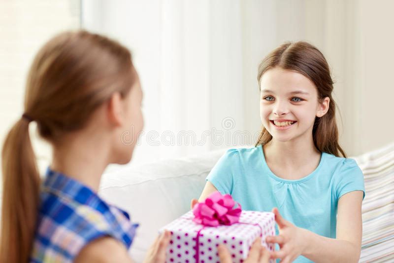 Happy little girls with birthday present at home. People, children, holidays, friends and friendship concept - happy little girls with birthday present sitting stock images