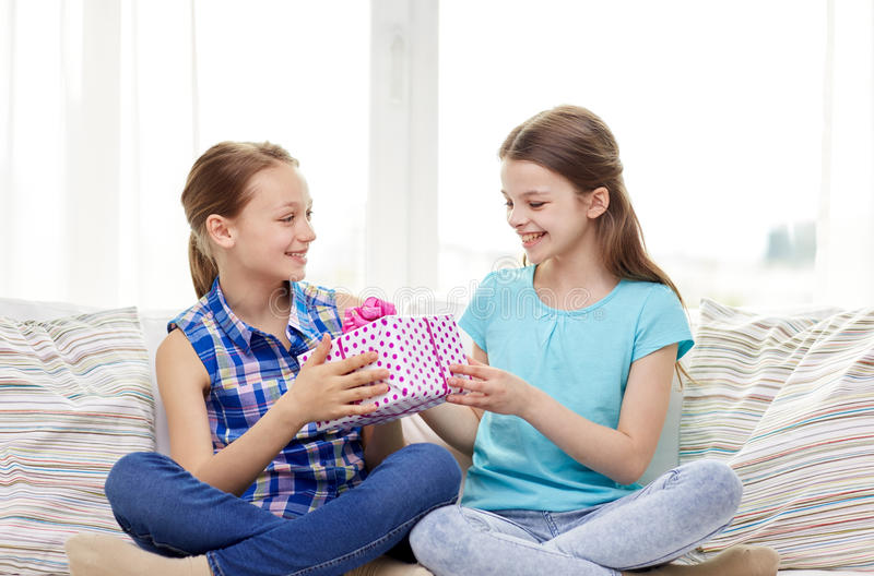 Happy little girls with birthday present at home. People, children, holidays, friends and friendship concept - happy little girls with birthday present sitting stock image