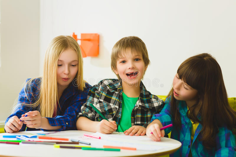 Happy Little girls and boy drawing pictures. Indoor at room.  royalty free stock photos
