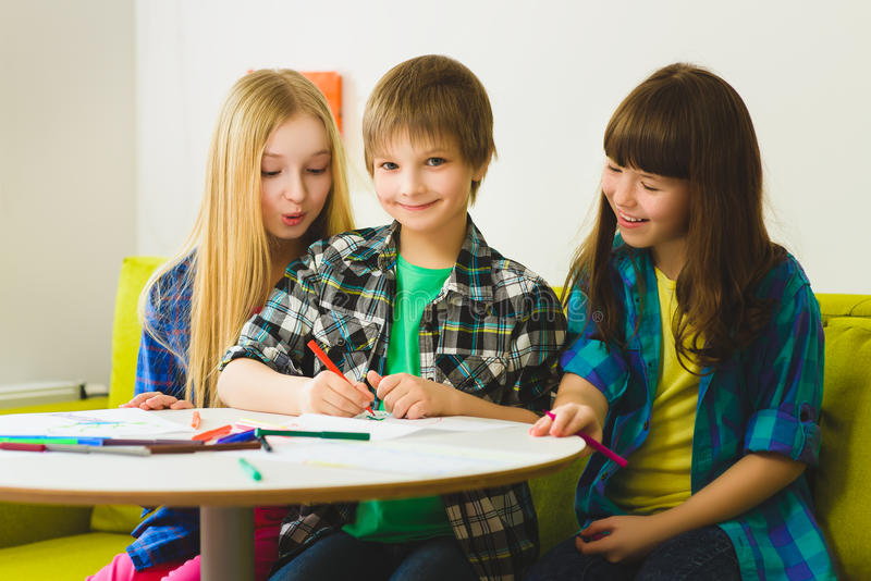 Happy Little girls and boy drawing pictures. Indoor at room.  stock photography