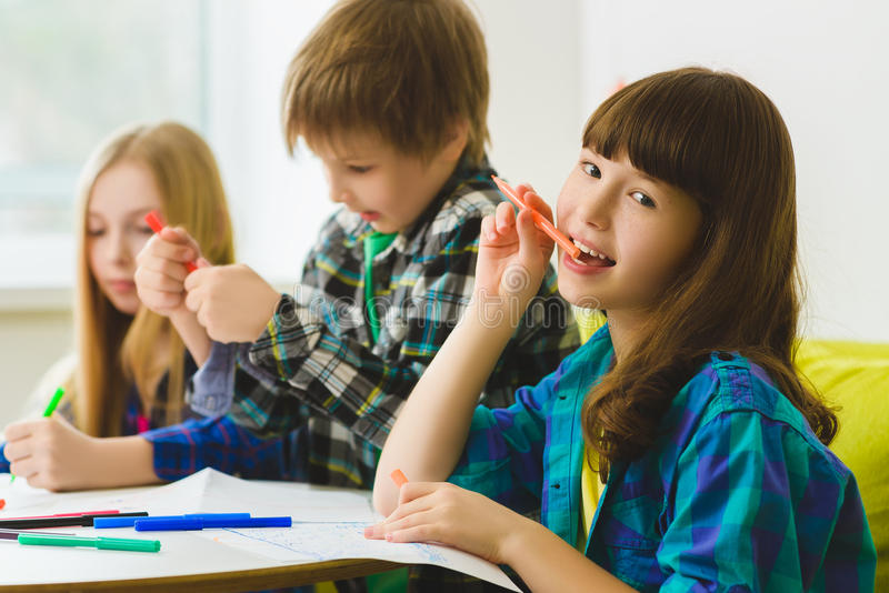 Happy Little girls and boy drawing pictures. Indoor at room. Girl dreaming in front of children stock photography