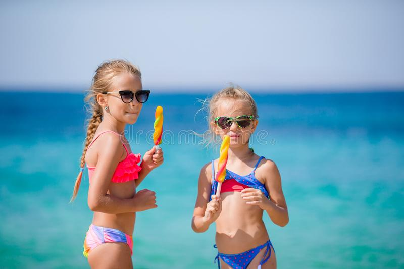 Happy little girls eating ice-cream during beach vacation. People, children, friends and friendship concept royalty free stock photography