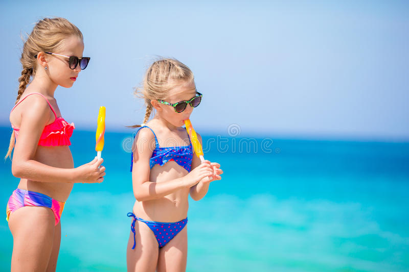 Happy little girls eating ice-cream during beach vacation. People, children, friends and friendship concept. Happy little girls eating ice-cream over summer stock image
