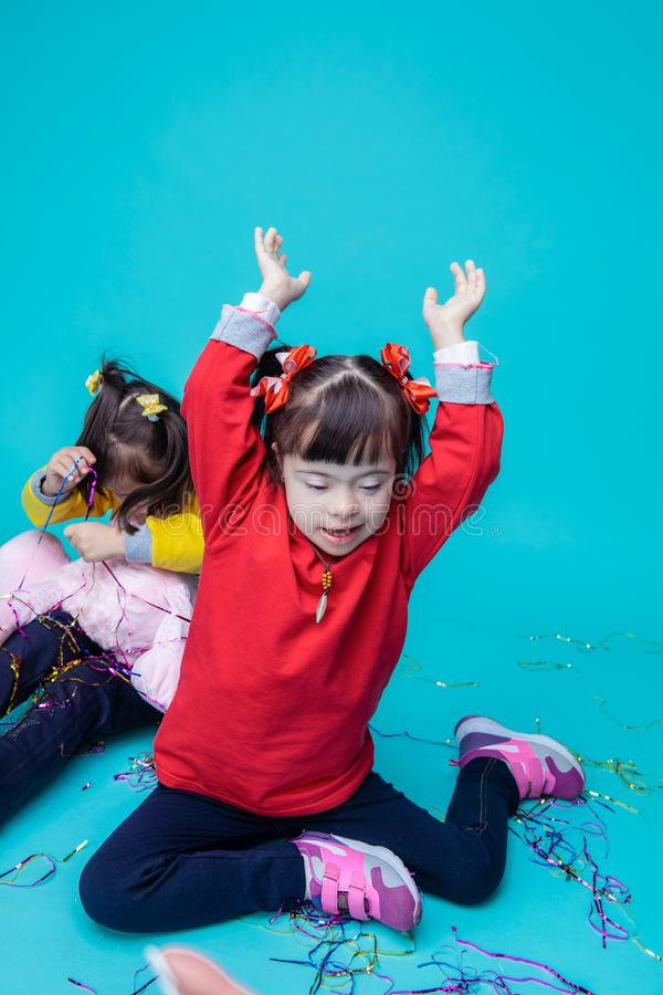 Happy little girls with genetic disorder playing with toys royalty free stock photo