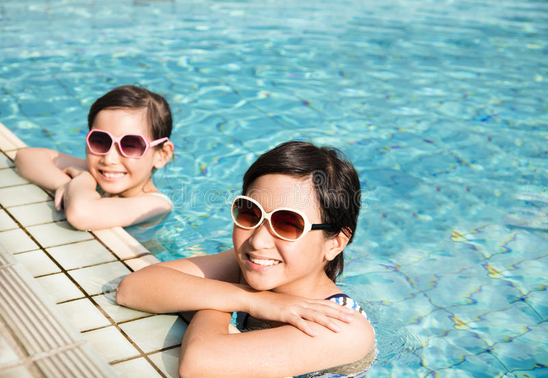 Happy little girls having fun in swimming pool stock images