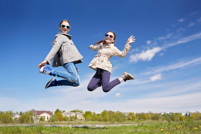 Happy little girls jumping high outdoors stock photos