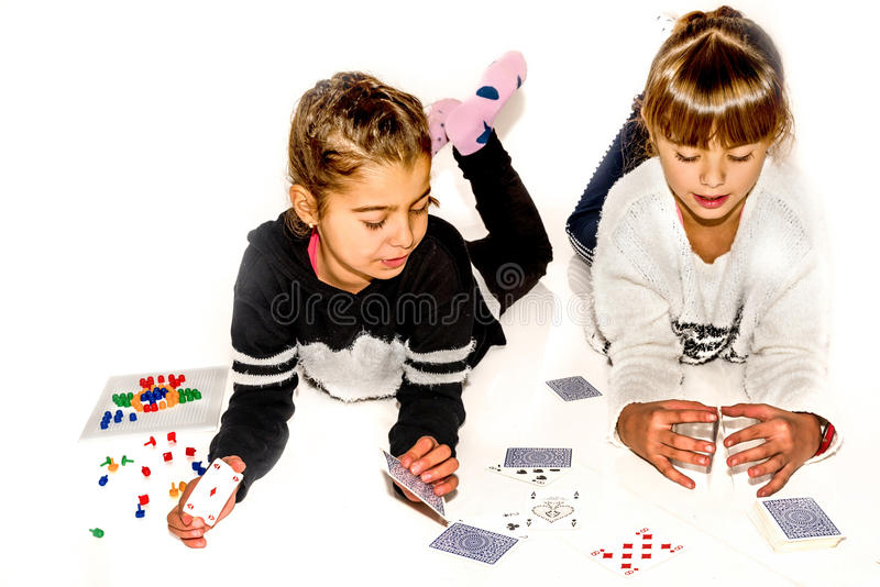 Happy little girls are making house of cards on white.  royalty free stock images