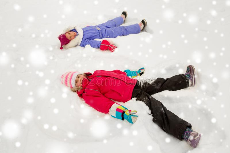 Happy little girls making snow angels in winter stock images