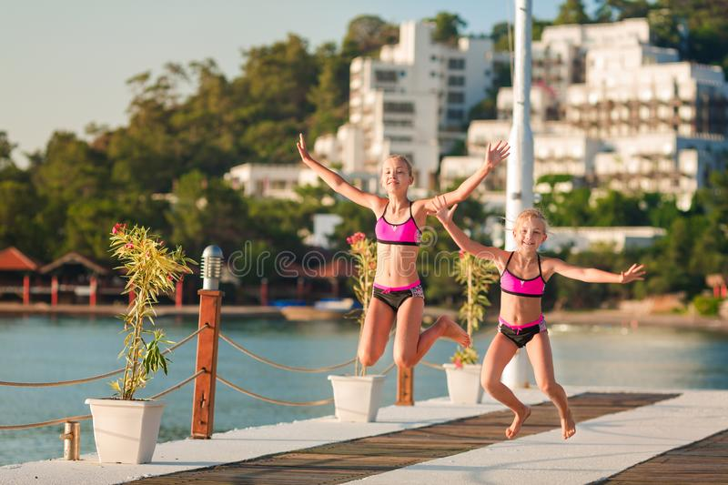 Happy little girls on the pier jumping royalty free stock image
