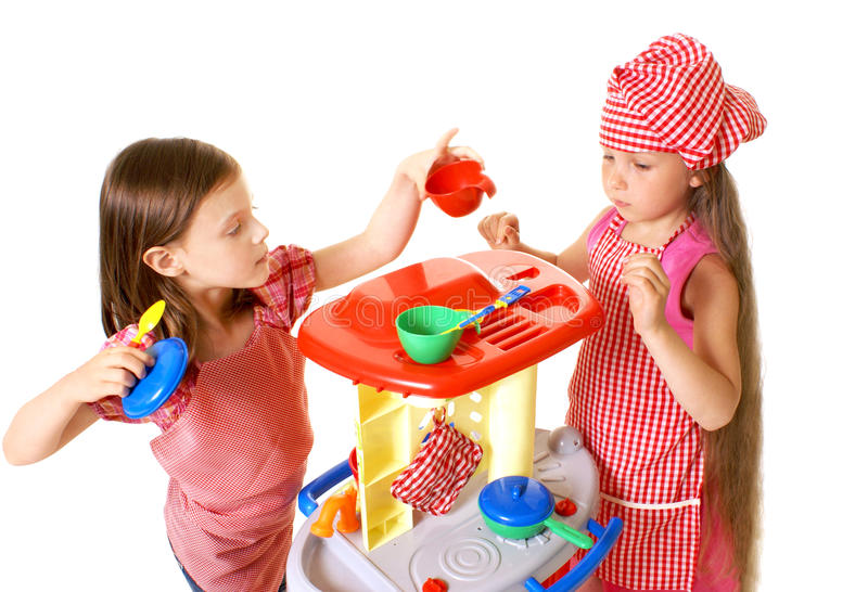 Happy little girls play cooking. Two charming little girls play with toys stock photos
