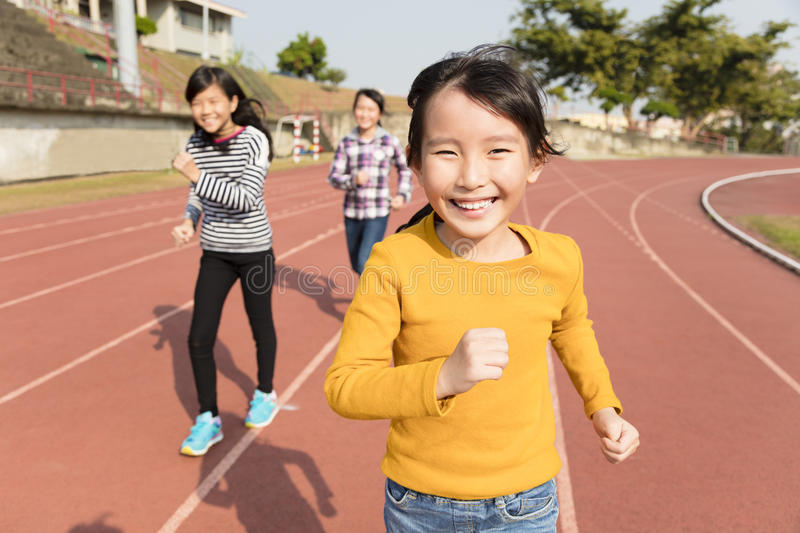 Happy little girls running on the track stock photo