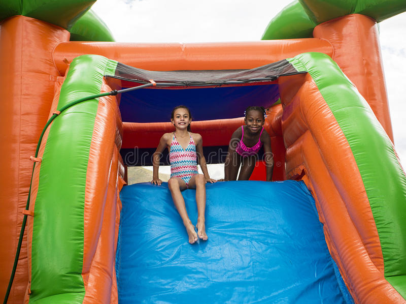Happy little girls sliding down an inflatable bounce house. Cute smiling little girls playing on an inflatable bounce house outdoors. She is screaming while royalty free stock photos