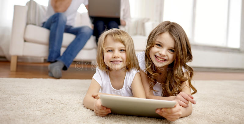 Happy little girls with tablet pc computer at home. People, family, technology and children concept - happy little girls playing with tablet pc computer at home royalty free stock photos