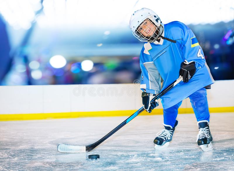 Happy little hockey player passing the puck. Portrait of happy boy, little hockey player, standing on ice rink and passing the puck royalty free stock image