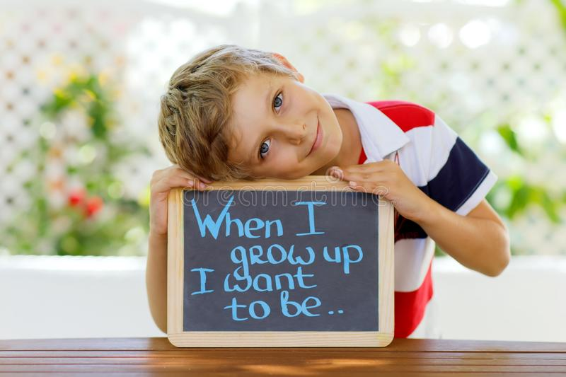 Happy little kid boy with chalk desk in hands. Healthy adorable child outdoors On desk When I grow up I want to be in royalty free stock images