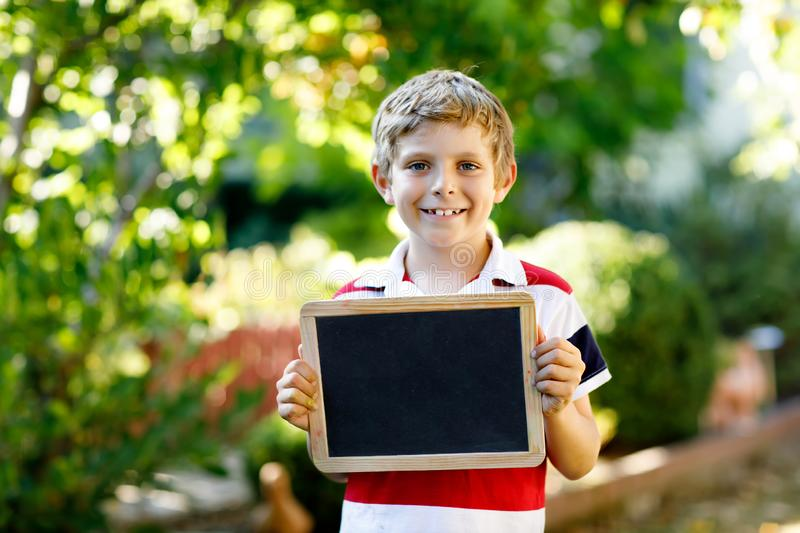 Happy little kid boy with chalk desk in hands. Healthy adorable child outdoors Empty desk for copyspace holding by. Beautiful schoolkid stock image