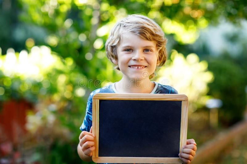 Happy little kid boy with chalk desk in hands. Healthy adorable child outdoors Empty desk for copyspace holding by stock photography