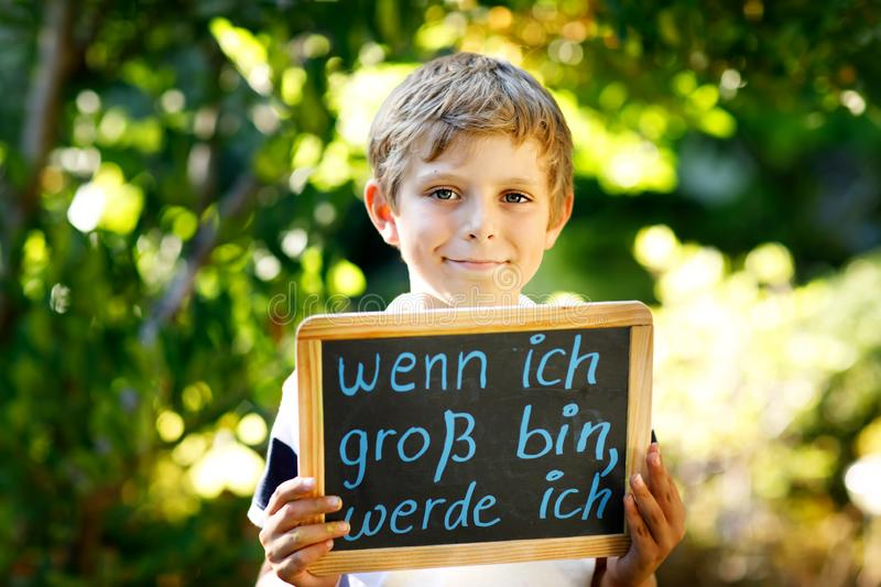 Happy little kid boy with chalk desk in hands. Healthy adorable child outdoors On desk When I grow up I want to be in. German with dream profession stock photo