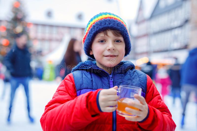 Happy little kid boy in colorful warm clothes on skating rink of Christmas market or fair drinking hot punch or. Chocolate. Healthy child having fun on ice royalty free stock images