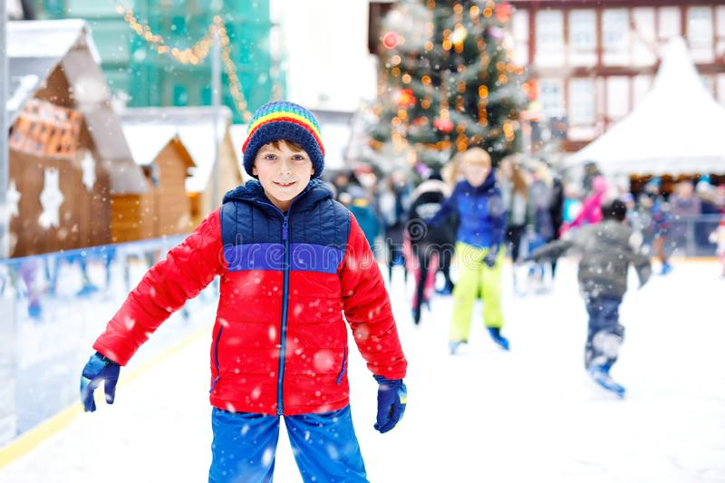 Happy little kid boy in colorful warm clothes skating on a rink of Christmas market or fair. Healthy child having fun on. Ice skate. Lot of people celebrating stock photography