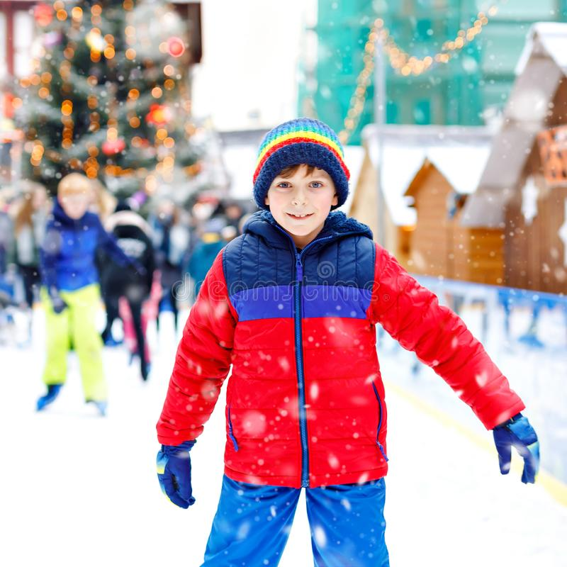 Happy little kid boy in colorful warm clothes skating on a rink of Christmas market or fair. Healthy child having fun on royalty free stock photo