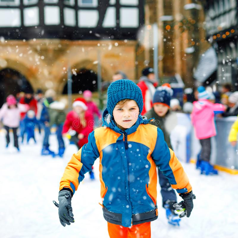Happy little kid boy in colorful warm clothes skating on a rink of Christmas market or fair. Healthy child having fun on royalty free stock image