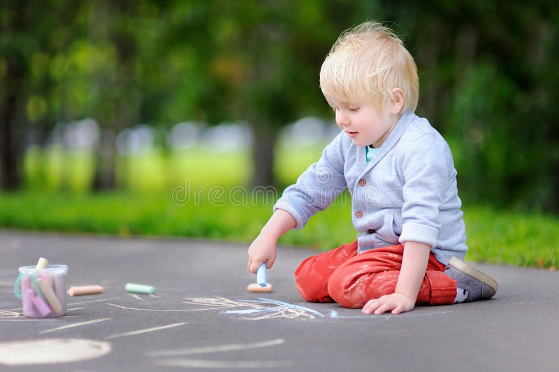 Happy little kid boy drawing with colored chalk on asphalt. royalty free stock photography