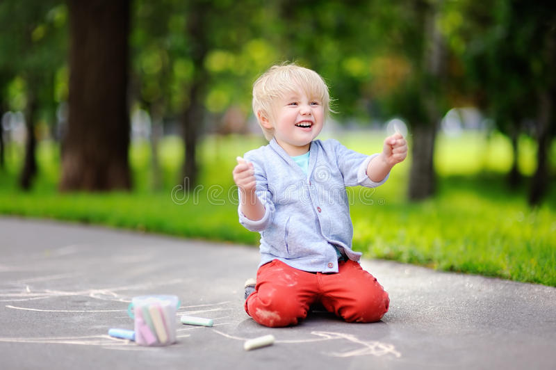 Happy little kid boy drawing with colored chalk on asphalt. royalty free stock photos