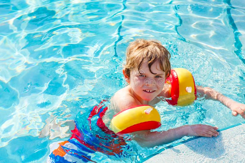 Happy little kid boy having fun in an swimming pool. Active happy child learning to swim. with safe floaties or swimmies. Family, vacations, summer concept royalty free stock photos