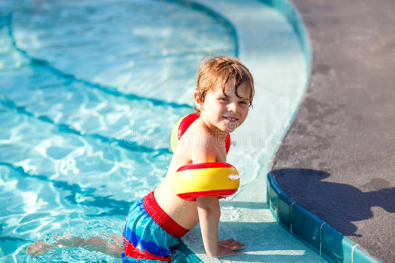 Happy little kid boy having fun in an swimming pool. Active happy child learning to swim. with safe floaties or swimmies. Family, vacations, summer concept stock images