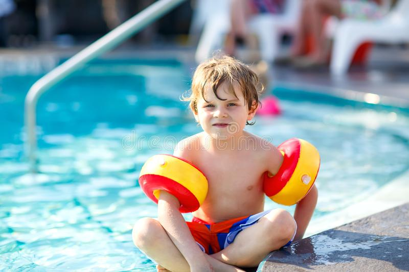 Happy little kid boy having fun in an swimming pool. Active happy child learning to swim. with safe floaties or swimmies. Family, vacations, summer concept royalty free stock photography