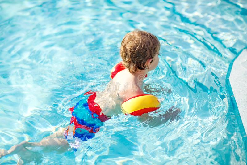 Happy little kid boy having fun in an swimming pool. Active happy child learning to swim. with safe floaties or swimmies. Family, vacations, summer concept royalty free stock image